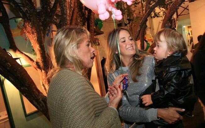 Adriane Galisteu entrega balão de bichinho para Rafaella no colo da mãe, Ticiane Pinheiro