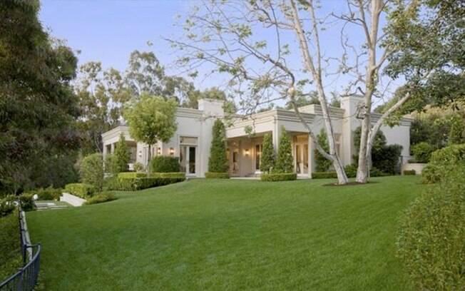 A contemporânea propriedade é cercada por grandes gramados e possui diversas varandas e terraços