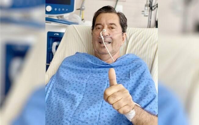 Maguito deitado em cama de hospital com sonda no nariz e fazendo 'joinha' com o dedo