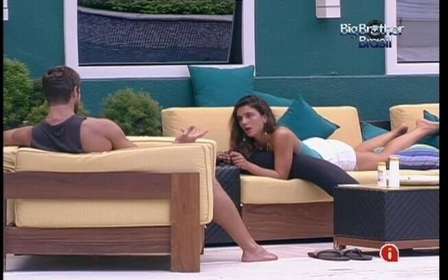 Jonas e Laisa conversam na varanda sob os olhares de Yuri