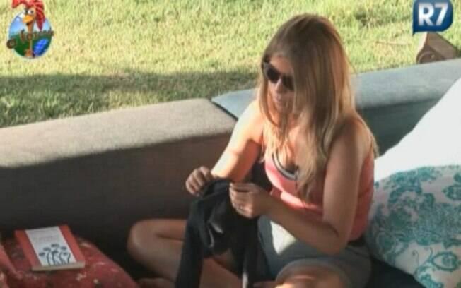 Raquel Pacheco costura uma calça preta no sofá da varanda
