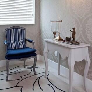 A arquiteta Janete Chaoui apostou em uma poltrona e no papel de parede para deixar o hall confotável