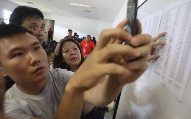 Familiares conferem lista com nomes dos tripulantes e passageiros do voo da AirAsia desaparecido. Foto: AP Photo/Trisnadi