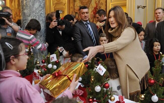Sem a filha Giulia, Carla Bruni distribui presentes para crianças