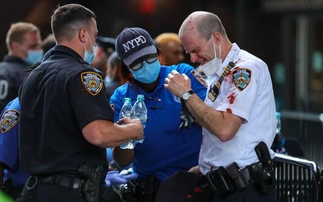 Policial ferido durante manifestação em Nova York é atendido por paramédicos. Foto: William Volcov/Brazil Photo Press/Agencia O Globo