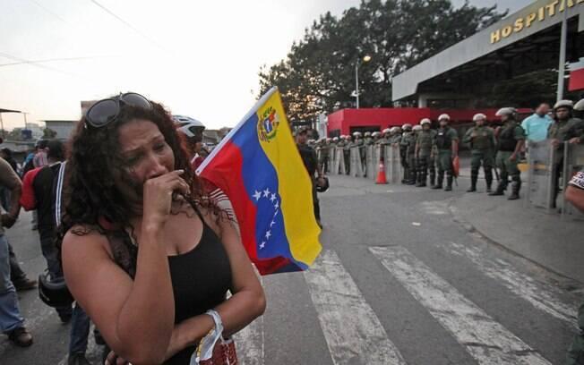 Mulher chora na frente do hospital militar em Caracas onde Hugo Chávez morreu (05/03)