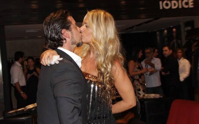 Adriane Galisteu beija o marido na reinauguração da loja do sogro nessa quarta-feira (11), em São Paulo