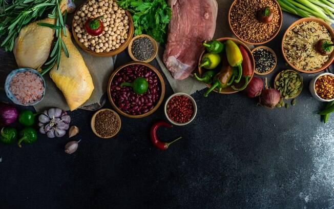 Vista superior de potes com legumes, vegetais, temperos e carnes sobre um balcão preto