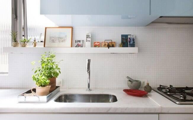 O armário em azul claro contrasta com leveza com o branco predominante