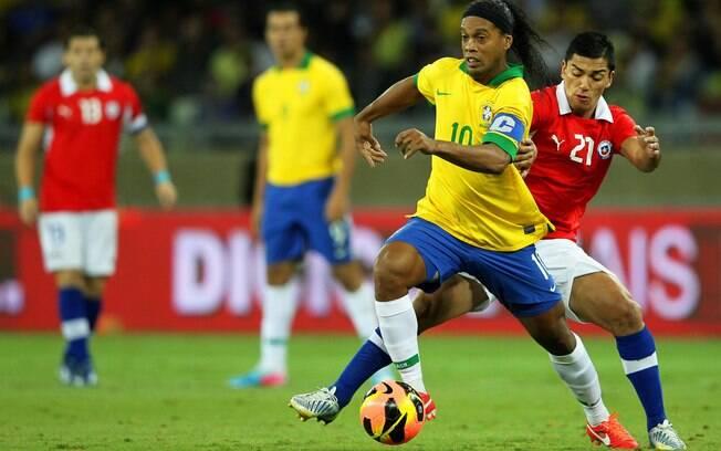 Ronaldinho protege a bola da marcação chilena