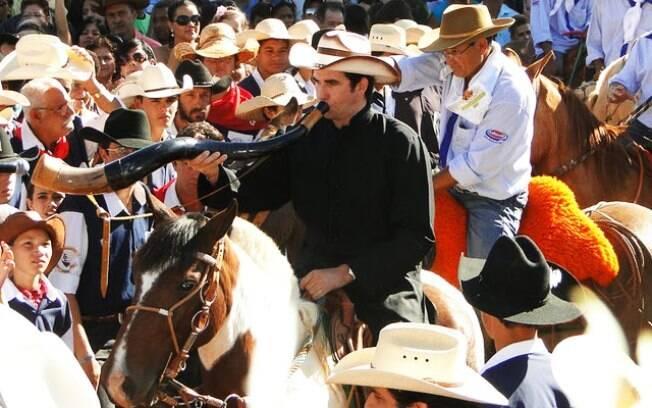 A cavalo, chapéu de vaqueiro na cabeça, berrante na mão, o Padre Junior Periquito convoca os fiéis para as celebrações da 'missa sertaneja', em Goiás
