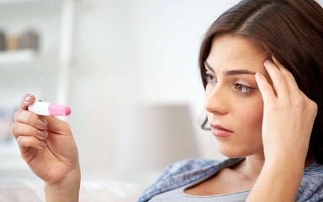 mulher olhando preocupada para teste de gravidez