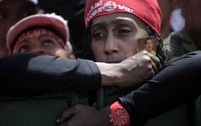 Mulher segura pequena foto de Hugo Chávez durante cortejo fúnebre do presidente venezuelano em Caracas (06/03)