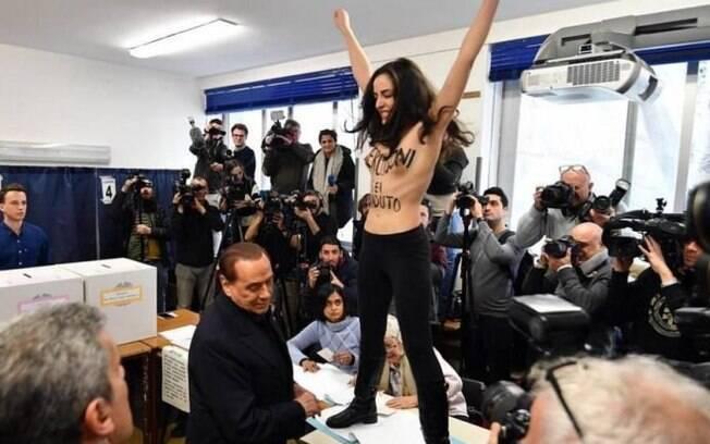 Ativista feminista protesta contra Berlusconi em momento que ex-primeiro-ministro italiano estava votando