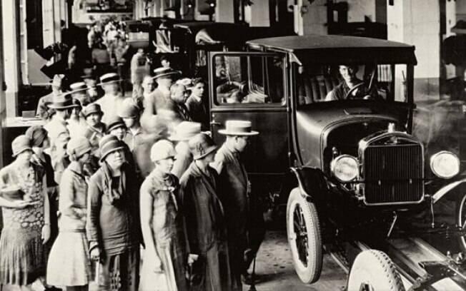 Foto histórica mostra visitantes admirando o Modelo T na linha de montagem da Ford na Rua Solon