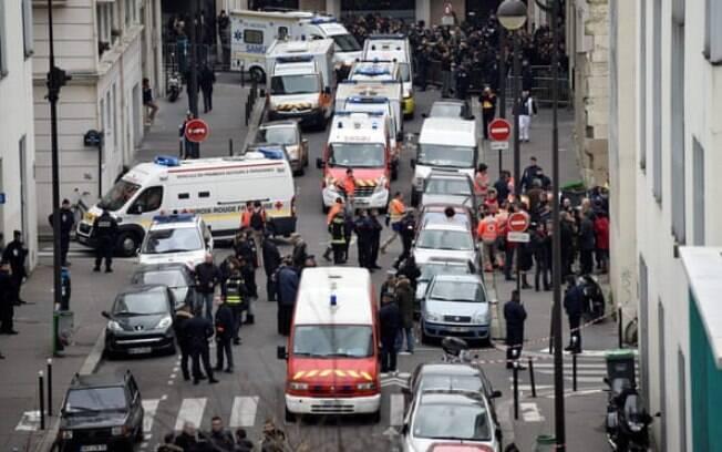 Bombeiros, policiais e equipes forenses fora dos escritórios do Charlie Hebdo em Paris em 7 de janeiro de 2015
