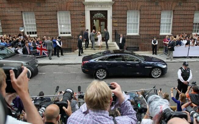 Fotógrafos e curiosos observam Charles e Camila entrarem na maternidade, enquanto aguardam saída de Kate e o bebê