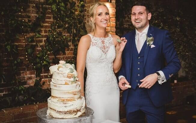 Depois da queda do bolo de casamento, o casal o 'reconstruiu' e tirou uma foto ao lado da sobremesa em pedaços