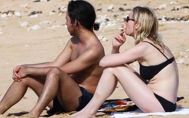 Kirsten fuma um cigarro ao lado de amigo em praia no Havaí
