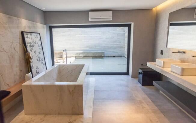 O espaço monocromático de 325 m² integra living, quarto, banheiro, cozinha e área externa com espelho d'água