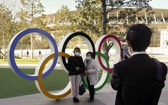 Turistas posam em frente aos anéis olímpicos em Tóquio%2C no Japão