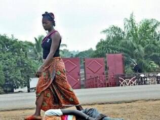 Mulher passa por uma suposta vítima do vírus ebola, na Libéria
