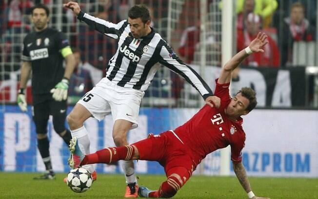 O zagueiro Barzagli (esq.) disputa bola com o  atacante Mandzukic