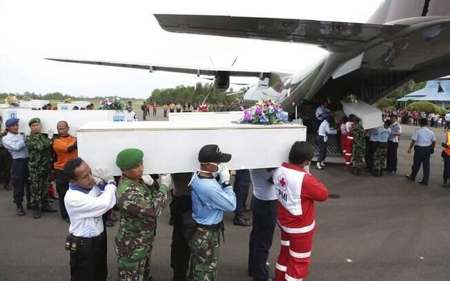 Equipe de busca carrega caixões com os corpos de vítima de acidente, nesta sexta-feira (2)