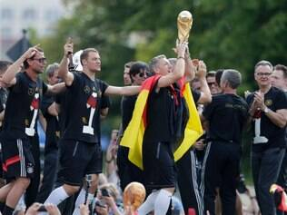 ESPORTES - 15.07.2014 Germany Soccer WCup Arrival Bastian Schweinsteiger lifts the trophy during a fan party after the arrival of the German national soccer team in Berlin Tuesday, July 15, 2014. Germany beat Argentina 1-0 on Sunday to win its fourth World Cup title. ( AP Photo/Petr David Josek )