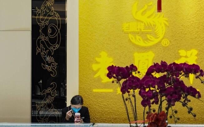 A funcionária de uma loja chinesa, com máscara de proteção, é vista em uma loja vazia na cidade de Guangzhou