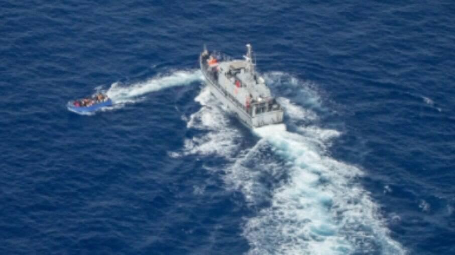 Um barco de imigrantes superlotado tenta escapar da guarda costeira da Líbia no Mar Mediterrâneo em 30 de junho