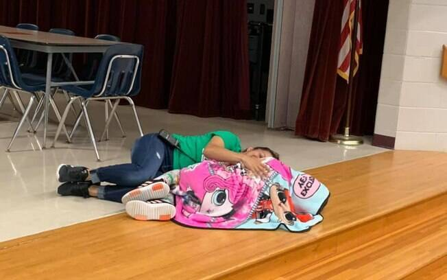 auxiliar escolar deita no chão para acalmar menina com autismo