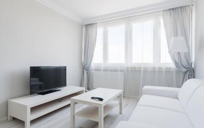 A cortina e os móveis claros ampliam o ambiente e deixam a sala pequena parecendo ser bem maior