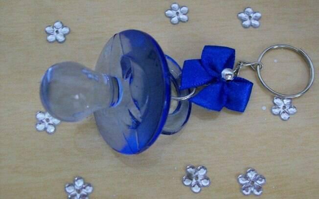 Um chaveirinho de acrílico em formato de chupeta azul para os convidados  lembrarem do chá de