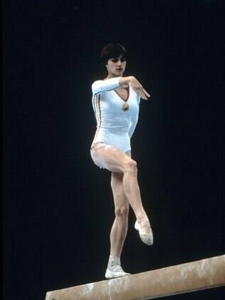 A legendária ginasta romena Nadia Comaneci se exercita na barra fixa nos Jogos de Moscou