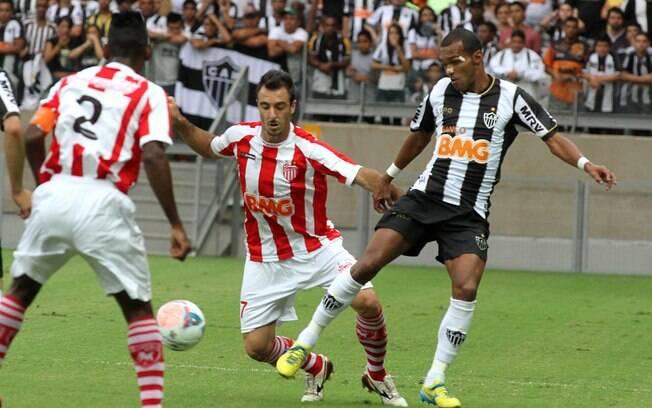 Richarlyson tenta passar pela marcação do  Villa Nova em jogo do Campeonato Mineiro
