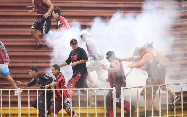 Torcedores do Atlético-PR correm para fugir da fumaça após briga com vascaínos