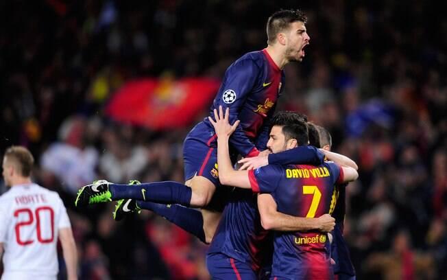 Piqué salta por cima de companheiros na  comemoração do gol de Messi logo no início da  partida contra o Milan