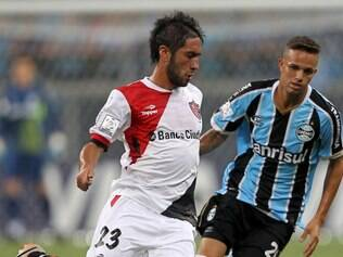 Hernan Villalba of Argentina's Newell's Old Boys, left, fights for the ball with Luan of Brazil's Gremio during their Copa Libertadores soccer match in Porto Alegre, Brazil, Thursday, March 13, 2014. (AP Photo/Nabor Goulart)