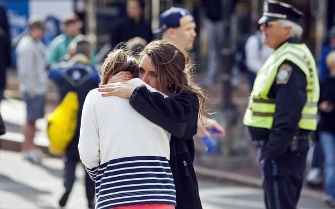 Mulher conforta outra aparentemente ferida após explosões na maratona de Boston, EUA (15/04). Foto: Reuters