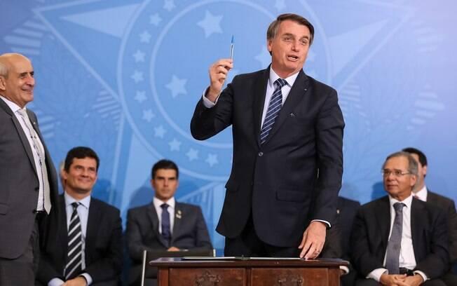 Bolsonaro segurando caneta na mão