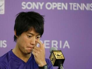 tKei Nishikori, of Japan, looks down at a news conference after withdrawing from his semifinal match against Novak Djokovic due to a left groin injury at the Sony Open tennis tournament, Friday, March 28, 2014, in Key Biscayne, Fla. (AP Photo/Lynne Sladky)