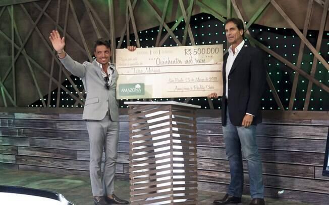 Victor Fasano, apresentador do reality, entrega o cheque para Tarso Marques