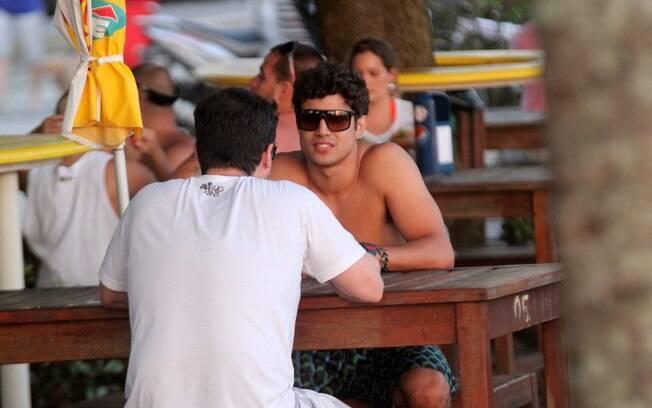 Caio Castro conversa com amigo em quiosque