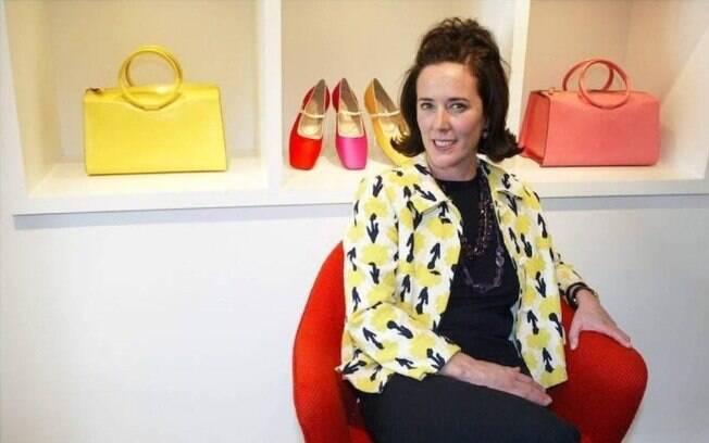 A estilista Kate Spade posando para foto atrás de algumas bolsas