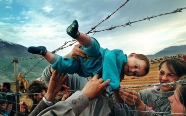 Kosovo. É dada permissão para que menino seja passado pela cerca do campo de refugiados para se juntar aos seus avós