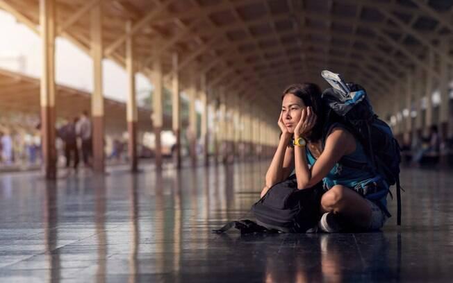 Viajante sentada no chão, com uma expressão de frustração.