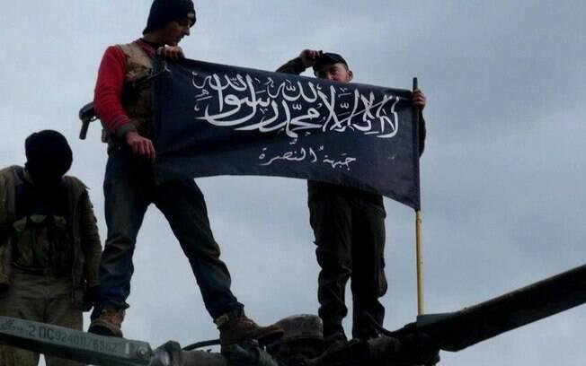 Rebeldes da Frente al-Nusra, afiliada à Al-Qaeda, seguram sua bandeira no topo de helicóptero da Força Aérea da Síria na base de Taftanaz (11/01)
