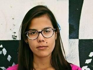 Olívia Paixão, uma das organizadoras do evento, posa com cartaz de campanha de alerta sobre a violência crescente contra transexuais e travestis