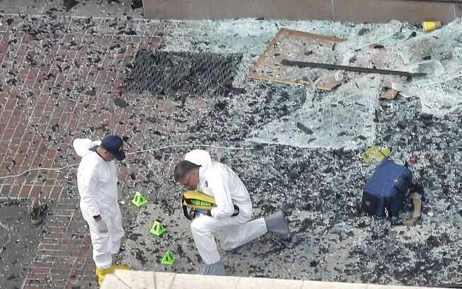 Investigadores numeram vidros destruídos e destroços em local da explosão de primeira bomba na Maratona de Boston (16/04). Foto: AP